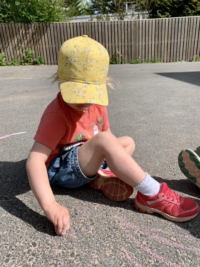 Child sitting on the asphalt